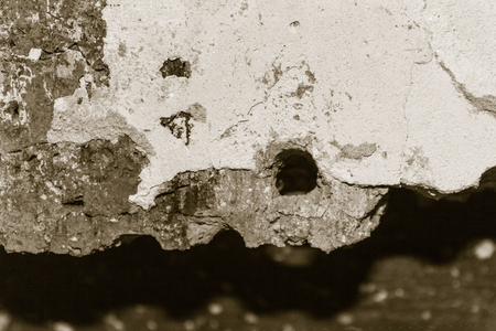 Concrete, cement, brick surface, wall. Cracks, chips, in the center a round hole. The background is blurred.