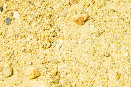 Sandy background, texture, bright sunlight. The coast, beach vacation, summer is in full swing. Light, yellow tones, large grains of sand.