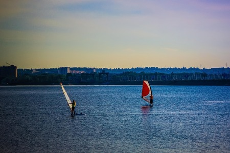 Two windsurfers on the water in the city. Summer, early evening. A modern sport. There are trees and an urban landscape in the distance. Foto de archivo
