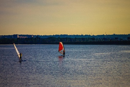Two surfers under sail, young people, romance. Blue water, illumination by the last rays of the sun. In the distance, city buildings. Natural lighting, toning. Imagens