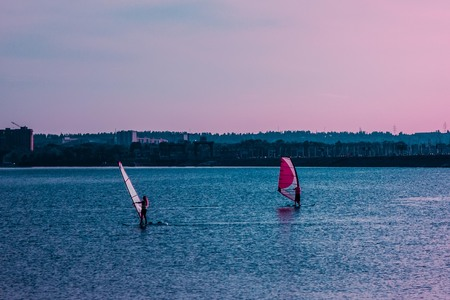 A summer evening in the city, a blue water surface, a lake, a river, a harbor, a bay. A guy and a girl on surf, under sail. Active lifestyle, romance, youth. Toning, copy space.