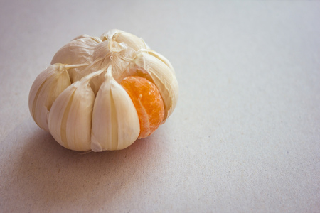 Large garlic onion with one orange slice of mandarin. Strange person, not like the others, odd man out. Hostility, another team. Daylight. Stock fotó