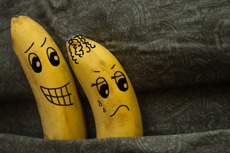 Two bananas in one bed. A man wants sex, a woman against. Unwillingness, not love, coldness, frigidity, lack of attraction. Dark background, the picture is made by the author.