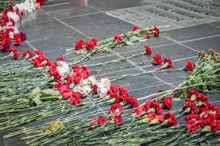 Memorial, eternal memory of the heroes of war, Victory Day. Red, scarlet flowers on gray granite, marble. Daylighting, vignetting. Stock Photo