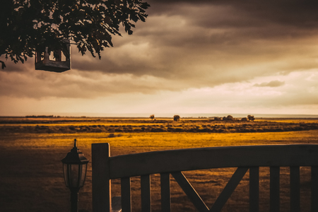 Yellow field, cloudy sky, in the foreground a wooden bench, a lantern. Country estate, vintage style. Calm, silence, autumn of life. Muted colors, retro toning. Stock Photo