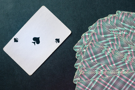 Card deck face down. Near the peak ace. Symbol of power, power, influence. Help an important person, danger. Dark background, top view.