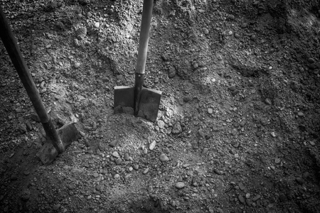 Two spades stuck into the ground. Heavy, unskilled labor. View from above. Black and white tones, vignetting.
