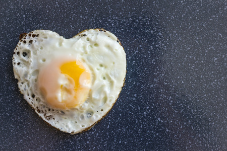 On a dark background fried egg, heart shape. Simple home menu, cooking with the soul. Daylight, top view. Stock Photo