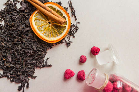 Additives to traditional black tea. Collection variety, large, selected leaves. Near raspberry, orange and cinnamon. Light background, top view.