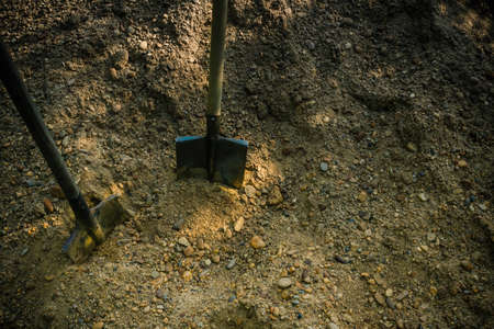 A pile of sand, earth, next to two shovels. Construction, housekeeping, landscaping. Heavy unskilled labor. Daylight, top view.