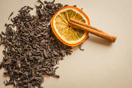 Dry large leaves of black tea, selected variety. Next to an orange slice and a cinnamon stick, aromatic additives. Preparation of a traditional drink, home comfort.