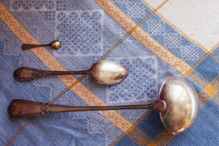 On the blue tablecloth are three different silver spoons. Women of different ages in the same family. House utensils, work in the kitchen, cooking. Daylight, top view.