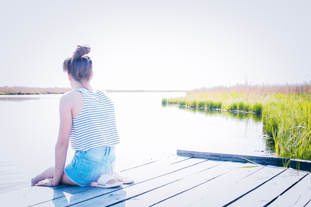 A young, modern girl sits on an old wooden pier, looking at the watery surface. A horizon line, a bright sky. Calmness, loneliness, reverie. Sunlight, copy space. Banco de Imagens