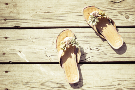 Summer slippers on a wooden background. Vacation, outdoor recreation, in the countryside. Bright sunlight, top view, copy space. 版權商用圖片