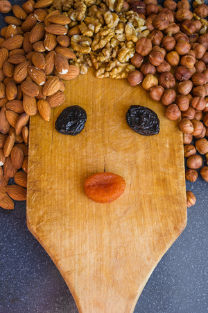 A funny face made of nuts and a wooden kitchen board. Lenten menu, vegetarianism, proper nutrition. Gray background, vertical arrangement. 스톡 콘텐츠
