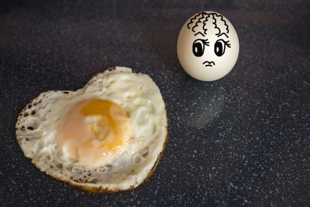 The white egg looks at the fried egg in the shape of a heart with perplexity. Unrequited feelings, coldness, lack of reciprocity. Dark background. The picture is made by the author.