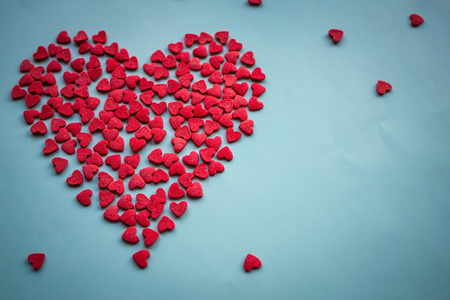 On a blue background a symbol of love, a red heart. Love message, recognition, tender affection. Top view, vignetting.