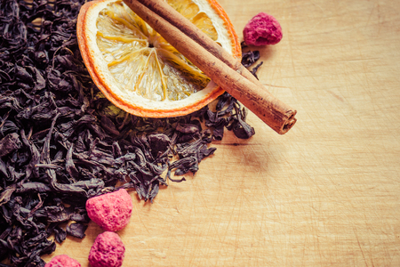 An old wooden surface, a kitchen board with traces of a knife. Top dry black tea, orange, cinnamon, raspberry. Daytime side lighting, copy space.