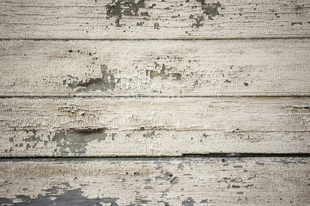 Old boards covered with light paint. Anomaly, repair is needed. Horizontal stripes. Wooden house, a fence, a wall. Daylighting, vignetting. Stock Photo
