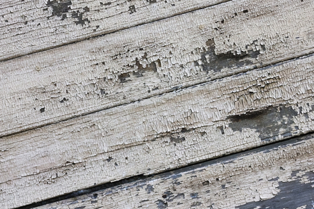 Dilapidated wooden boards, light paint faded, cracked, crumbled. Old age, desolation, poor condition. The bands are diagonal.
