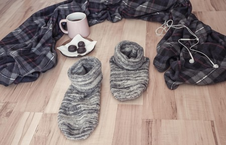 At home were your favorite things, plaid and socks. He went to look for himself, he left the comfort zone. Wooden background, daylight.