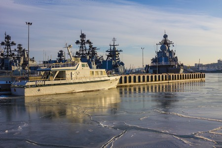 The city port, early morning. Military ships with modern equipment are on the roadstead in the harbor. The coastal strip, thin ice on the water, it's cold. Blue sky, sunlight.