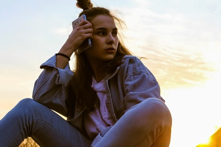 Young girl on the sky background. Long hair, face turned to the side. In the hands of the phone. Modern youth style, denim clothing. Blue and yellow tones. Bottom view.