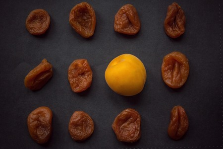 Among the old, dried, shriveled apricots is one fresh, juicy, young. Top view, dark background, vignetting.