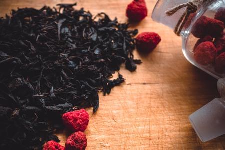 Dry black tea on an old wooden board, home kitchen. In a glass bottle, red berries, dried raspberries. Ingredients for a hot drink. Daytime side lighting, retro style. 版權商用圖片 - 107268954