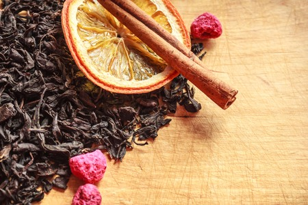 Dry black tea, collection variety, selected leaves. Nearby fruit supplements. A fragrant drink, a symbol of hospitality. Light wooden surface, old kitchen board.