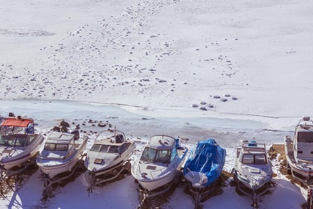 Small boats on an empty, snowy shore. The sea froze, covered with ice and snow. Dead season, waiting for the arrival of spring. Blue toning. View from above.
