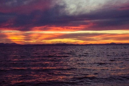 Dramatic sky, heavy thunderclouds. In the distance a crimson sunset, on the water red reflections of the sun. Premonition, clouds thicken, tension, glow. Stock fotó