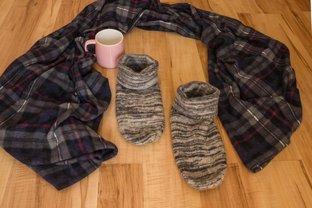 A cozy plaid, a house mug and warm socks on a wooden floor. Nobody here. Go away in search of yourself, leave your familiar surroundings. Daylight.