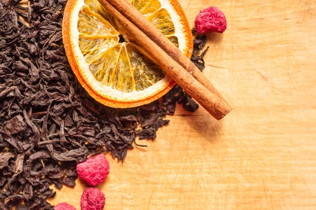 Large leaves of black, fermented tea, red raspberry, cinnamon stick, orange circle. A fragrant drink, a symbol of hospitality. Background of a wooden kitchen board, copy space.