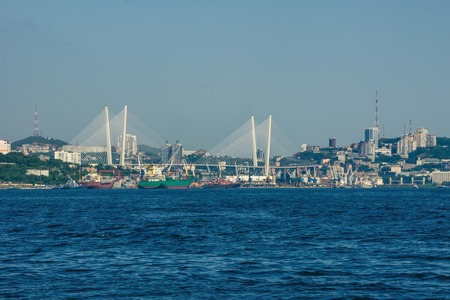 Vladivostok, a major city in the Far East, Russia. A large seaport, many merchant ships, cranes. High buildings in the distance. A clear, sunny day. Stock Photo