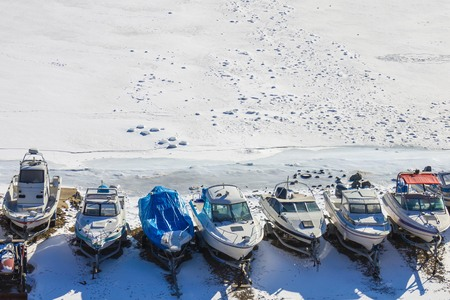 Marina, parking for yachts, boats. Snowy winter, the sea at the shore froze, everywhere white ice. Dead season, waiting for spring, anticipation.