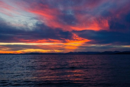 Bright, pink, orange sunset on the sea. Dark blue water, thunderclouds. Red, crimson tone. In the distance, the horizon, small hills.