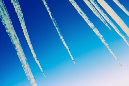Against the background of the blue sky, transparent icicles. End of winter, thaw, warming. Diagonal arrangement, bottom view, copy space. Stock Photo