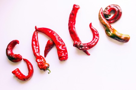 Bright red letters on a light background. Bitter, hot peppers. The inscription is made of pods. Sale, urgent, burning offer.