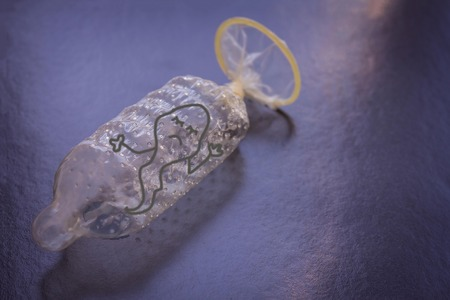 The condom is securely tied in a knot. Inside the sad sperm can not go outside. Dark background, blue toning. Copy space. Figure made by the author.