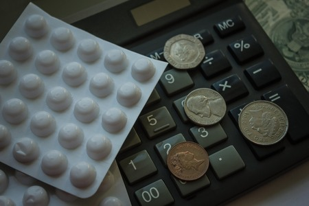 Calculator, small money and pill packaging. Expensive medicine, the cost of treatment. View from above.