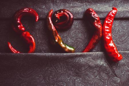 Le mot sur des draps sombres, la passion au lit. Lettres de poivron rouge, goût piquant. Tonification vintage, vue de dessus, espace de copie.