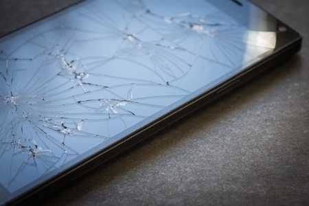 Broken phone, glass in cracks, blue sky reflected in the surface. Despairing, silence, loss of hope. The background is blurred. Vignetting, copyspace. Stock Photo