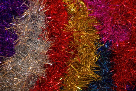 Bright, colored tinsel. Waiting for the holiday, preparation for the New Year. Colorful, cheerful decoration of the house, outfit for the Christmas tree. Archivio Fotografico
