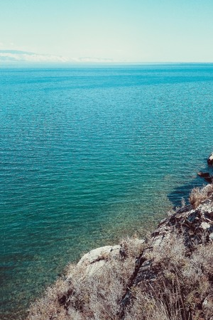 Seascape, view of the blue sea from the cliff. In the distance the horizon line, the sky. Bright solar lighting. Toning. Vertical layout.