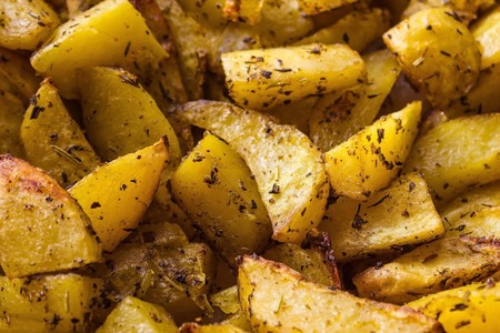Potatoes cooked in the oven. Large slices sprinkled with spices. Simple tasty dish. Warm yellow tones. The edges are blurred.