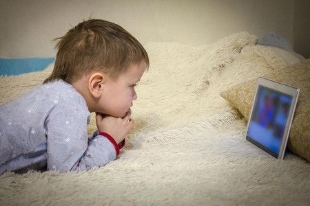In the childrens room, on the bed lies a boy in pajamas, looks at the laptop screen. Childrens leisure, computer addiction, harm to gadgets. Home furnishings, artificial lighting.