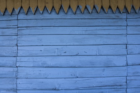 Wooden paneling, narrow blue boards, the wall of an old house. Faded colors, vintage style. Horizontal stripes, on top of a yellow decorative element. Handmade carpentry craft.