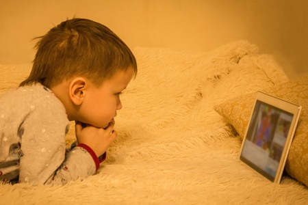 A little boy in pajamas looks at the laptop screen. Children and gadgets, computer addiction. Home furnishings, childrens bedroom. Artificial lighting, vignetting.