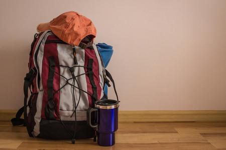 Wanderrucksack, thermoclean, kariert und orangefarbene Kappe. Dinge werden für Trekking, Reisen gesammelt. Annäherung an den Sommer, die Ferienzeit. Standard-Bild